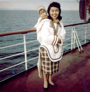 Photo of Inuk cultural interpretor Sarah Ekoomiak with the infant of a TB patient in her amaut taken aboard the C.D.Howe c.1964 where Sarah worked with DINA.
